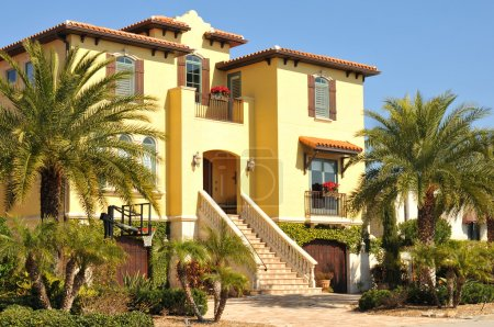 Beautiful three story spanish colonial home with ornate stairway leading to second story entryway.
