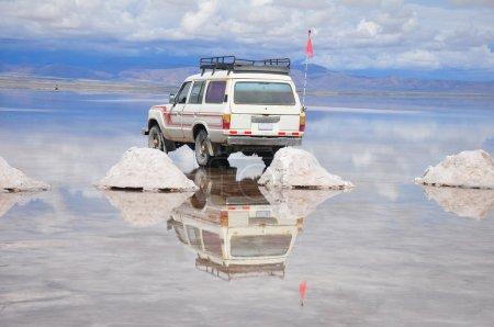 Photo pour Tour jeep et monticules de sel reflétés dans inondée Salar de Uyuni, Bolivie - image libre de droit