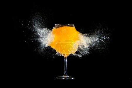 verre avec explosions de jus d'orange dans le fond noir