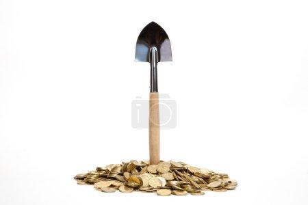 Photo pour Pelle debout dans un tas de pièces de monnaie à fond blanc - image libre de droit