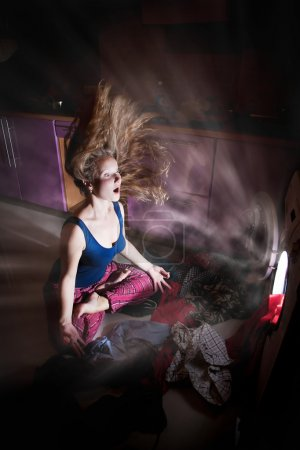 Photo for Astonish Woman in meditation pose near by washing machine glowing inside - Royalty Free Image