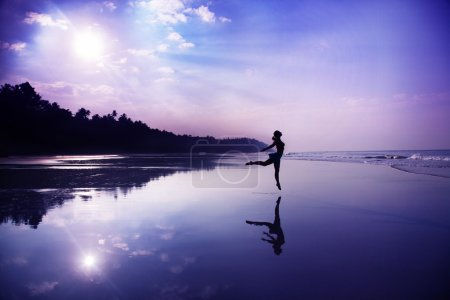Photo for Silhouette of a beautiful young girl dancing on the beach at the sunrise in purple colors - Royalty Free Image