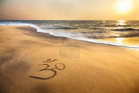 Om symbol on the beach