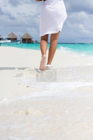 Foto de Una mujer joven va en una costa - Imagen libre de derechos