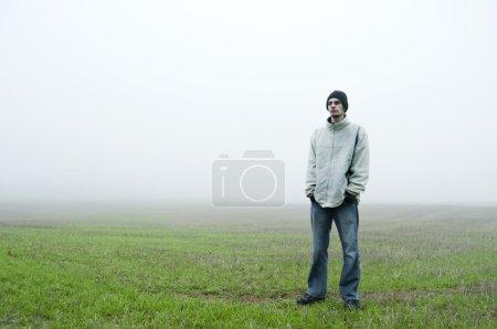 Photo pour Adolescent caucasien blanc se dresse dans un champ d'herbe verte avec un bonnet noir et une veste blanche sur ses mains dans son jeans bleu. Il est à la recherche vers le camer - image libre de droit
