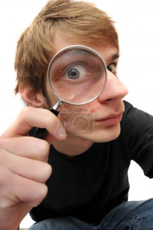 Photo for A young adult man looking down with a magnifying glass up to his eye, searching for just the right clue to crack the case of the mystery. - Royalty Free Image