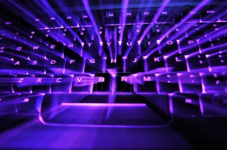 Photo pour Un pourpre clavier rétroéclairé rougeoyant lumineux avec éclatement de lumière entre les touches - image libre de droit