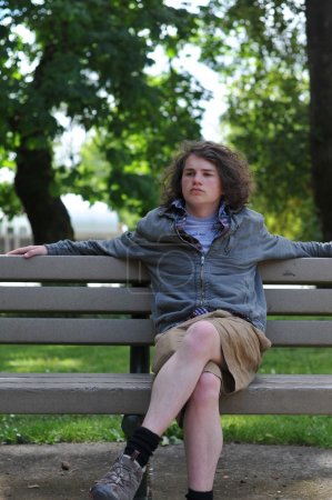Teenager sits on bench and relaxes while thinking
