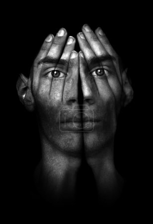Photo for Surreal dark portrait of a young man covering his face and eyes with his hands, but he can see right through them. - Royalty Free Image
