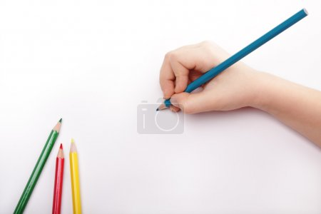 Photo for Child hand draws a blue pencil. White-gray background Above view. - Royalty Free Image
