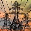 Energy towers on an electric sky background. 3D re...
