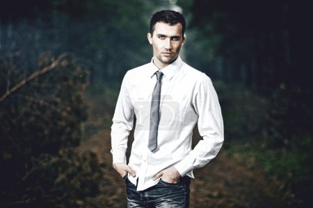 Stylized fashion portrait of young attractive man, outdoors