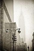 Old-fashioned stylization of silhouette of Empire State building in blizzar
