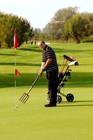 Photo pour Golfeur masculin drôle, jouer au golf avec fourche - image libre de droit