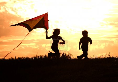 Photo for Two kids flying a kite at sunset invoke childhood memories. - Royalty Free Image
