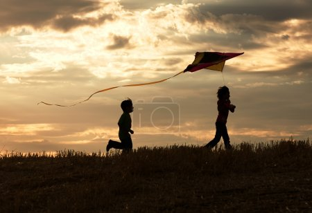 Photo for Two children enjoy flying a kite during sunset. - Royalty Free Image