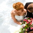 Bride holding a bouquet of flowers in her hand, th...
