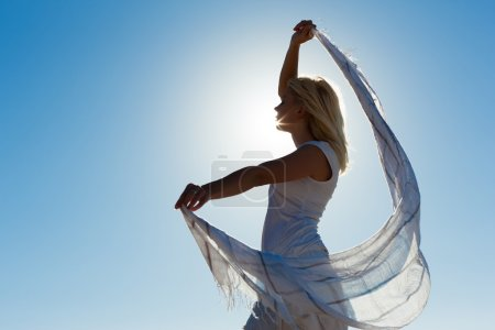 Photo for Woman with white scarf being backlit by the sun standing in the wind feeling happy and balanced - Royalty Free Image