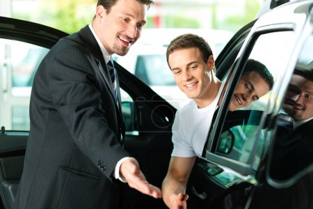Photo for Sitting in his new auto, the salesman talking to him and explaining details - Royalty Free Image