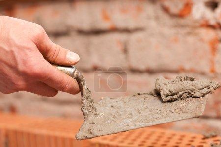 Photo pour Un mur, il met le coulis sur le dessus de briques - image libre de droit