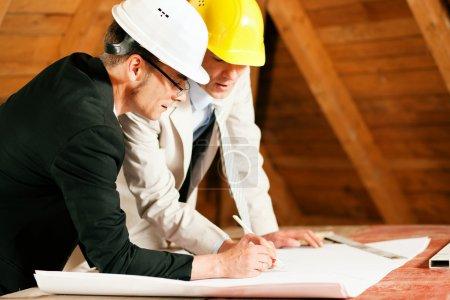 Photo pour Plans de discussion ingénieur ou arpenteur et bleus. tous deux portent des casques et sont trouvant sur le chantier de construction d'une maison à l'intérieur - image libre de droit