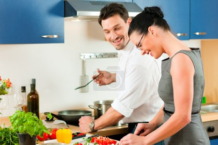 Photo for Man and woman in their kitchen at home preparing vegetables for salad and pasta sauce - Royalty Free Image