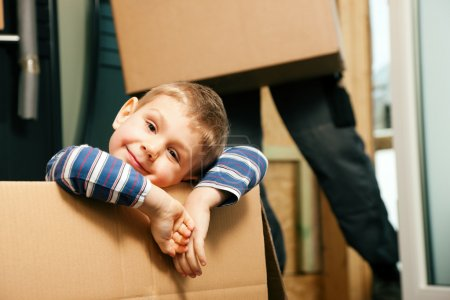 Photo for House. They are sitting in front of a stack of moving boxes being happy. Father is dressed in a way that can also represent a mover - Royalty Free Image