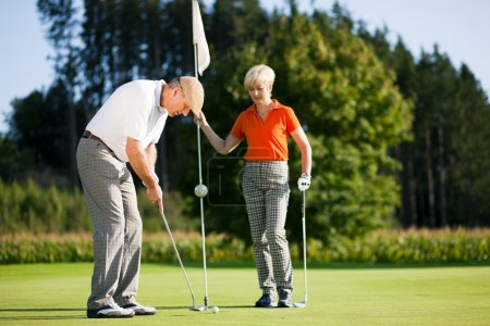 Senior couple playing golf on a