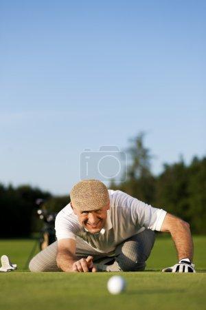 Senior man playing golf aiming