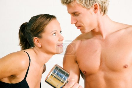 Couple in gym setting. He is