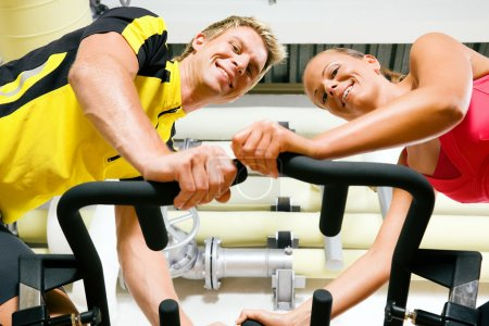 Couple exercising by spinning