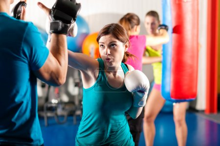 Photo for Trainer in a sparring session, in the background other boxers are hitting the sandbag - Royalty Free Image