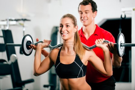 Woman in gym with personal