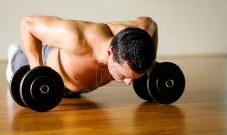 Strong man with dumbbells