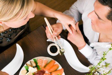Couple eating sushi for dinner