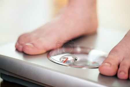 Photo for Standing on bathroom scale measuring her weight controlling her dieting results - Royalty Free Image