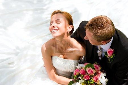 Photo pour Mariée tenant un bouquet de fleurs dans sa main, le marié l'embrassant - image libre de droit