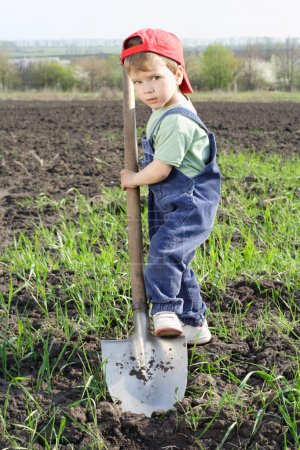 Little boy to dig on field with big shovel
