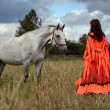 A gypsy-dressed girl interacts with a grey horse i...