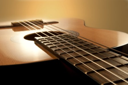 Photo for Close and low level angle capturing an acoustic guitar with warm brown background. Focus on foreground strings. - Royalty Free Image