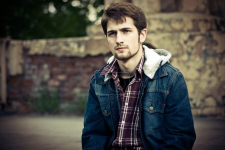 Photo pour Jeune homme portant des vêtements de jeans devant le mur fissuré en ruine . - image libre de droit