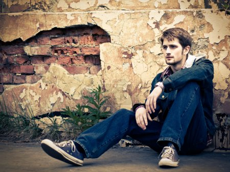 Photo for Young man wearing jeans clothes sits on the ground in front of the cracked ruined wall. - Royalty Free Image