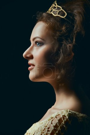 Profile of young woman on black background