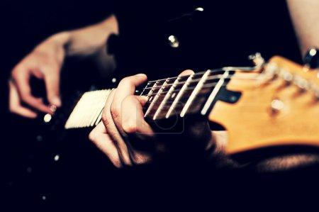Photo pour Gros plan de l'homme les mains sur la guitare - image libre de droit