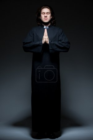 Young priest is praying against dark background