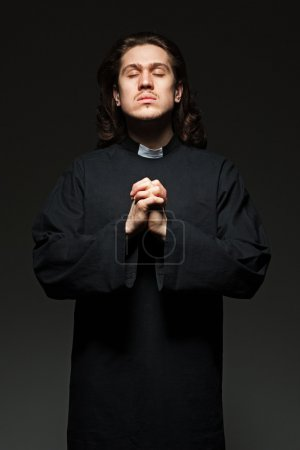 Young priest is praying