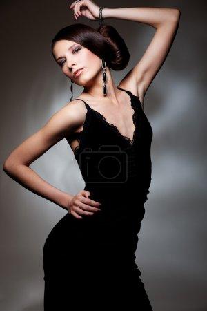 Photo pour Séduisante femme en robe noire posant sur fond sombre - image libre de droit