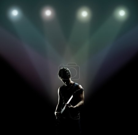 Photo for Young musician playing the guitar on the stage - Royalty Free Image