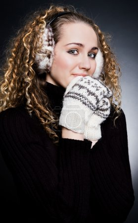 Beautiful blond in headphones and mittens