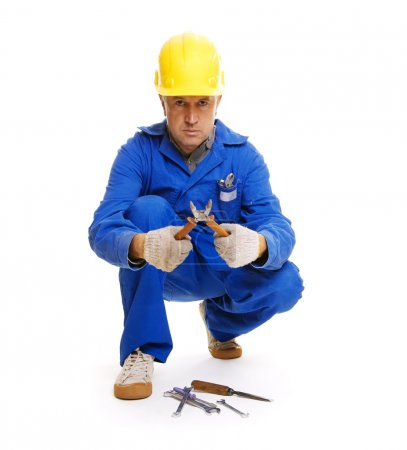 Handsome workman sitting on the floor with different tools